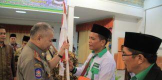 Foto: Kepala Satuan Polisi Pamong Praja (Satpol PP) Asren Nasution menyerahkan Pataka Merah Putih di Aula I Madinatul Hujjaj Asrama Haji Medan.