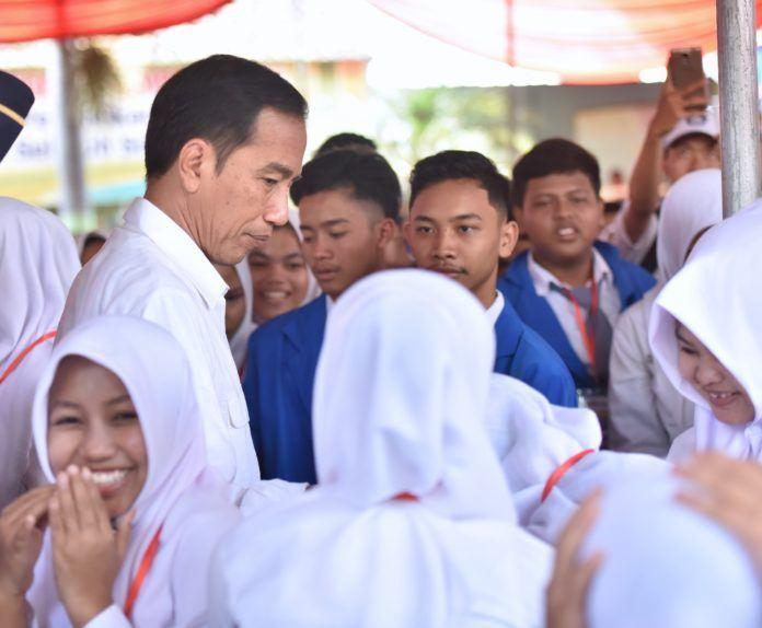 Foto: Presiden Jokowi di tengah siswa penerima KIP di SMP Negeri 7, Jalan Cenderawasih, Kabupaten Jember, Jatim, Minggu (13/8).