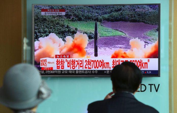 Warga menyaksikan penembakan rudal Korea Utara yang disiarkan televisi. (AFP)