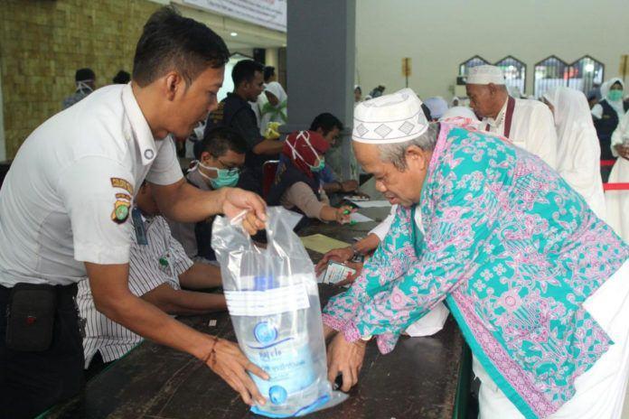 Foto: Jemaah haji asal DKI Jakarta menerima Air Zamzam setibanya di Debarkasi Jakarta - Pondok Gede (JKG).