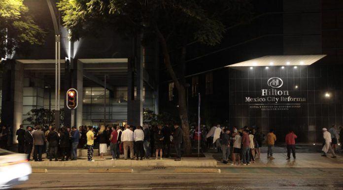 Sejumlah pengunjung keluar dari hotel saat terjadi gempa bumi di pusat kota Mexico City (7/9). Akibat gempa tersebut Survei Geologi AS mengeluarkan peringatan tsunami. (AFP Photo/Diana Ulloa)