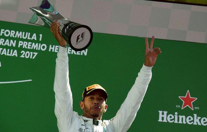 Pembalap Mercedes, Lewis Hamilton, mengangkat trofi yang diraihnya setelah menjuarai balap Formula 1 dalam Grand Prix Italia di Sirkuit Monza, Minggu, 3 September 2017. (AFP)