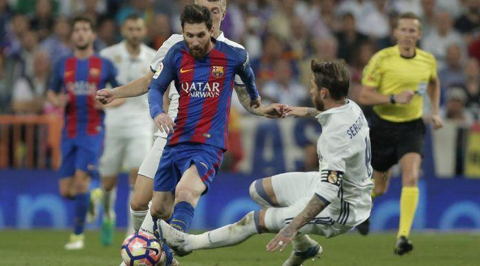 Lionel Messi mendapat adangan dari bek Real Madrid, Sergio Ramos dpada duel El Clasico di Santiago Bernabeu stadium, Madrid, Spanyol, Minggu, (23/4). Barcelona menang 3-2. (AP/Daniel Ochoa de Olza)