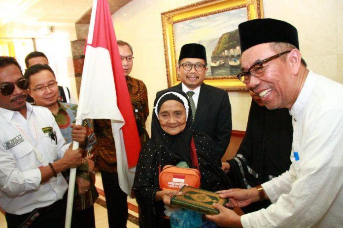 Foto: Sekjen Kemenag Nur Syam serahkan Al Quran kepada Jemaah Tertua saat pelepasan kloter terakhir.