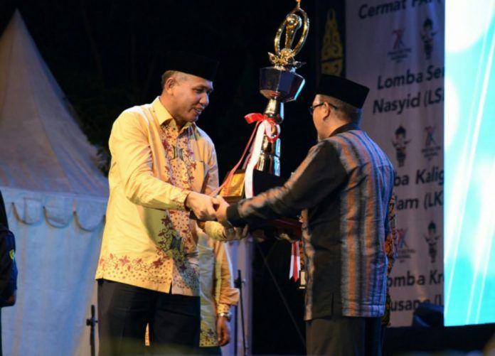 Foto: Wakil Gubernur Aceh, Nova Iriansyah menyerahkan piala juara umum kepada Kepala Kanwil Kemenag Provinsi Aceh, Daud Pakeh pada malam penutupan yang dipusatkan di Taman Sulthana Safiatudin Aceh, Jumat (13/10).
