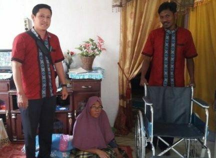 Syahrun SHI yang didampingi staf Baitul Mal kota langsa bapak Jul menyalurkan satu kursi roda kepada warga.